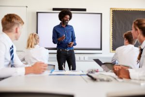 Male teacher standing in front of whiteboard talking to pupils