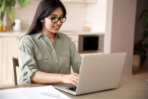 female teenager looking at laptop and making notes