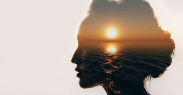 female head silhouette with sunset over sea reflection
